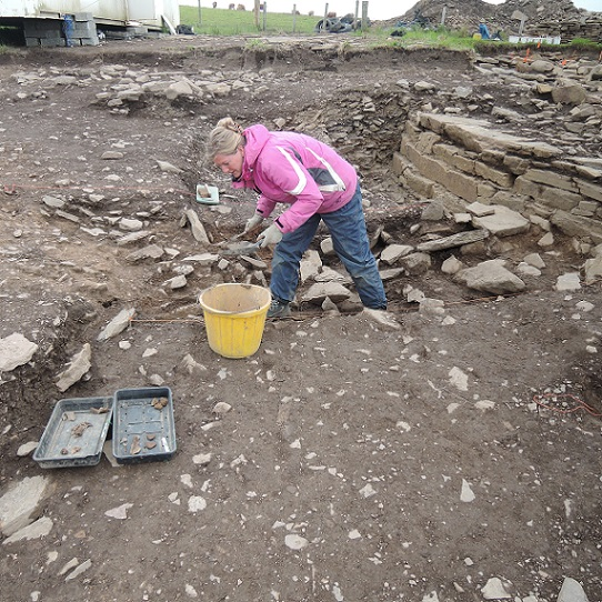 Hanneke excavating in the terrace cut around the broch exterior
